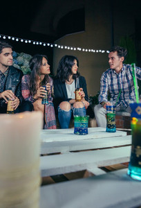 Group of friends talking and drinking in party
