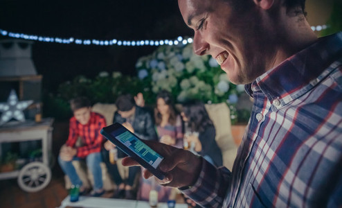 Happy man looking smartphone in a party with friends