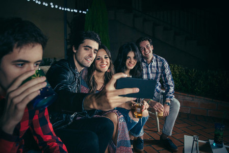 Happy friends taking selfie with a smartphone in party