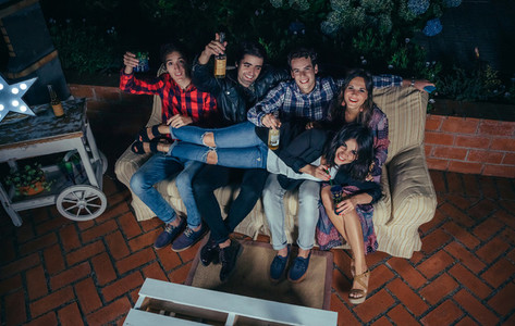 Woman lying over friends sitting on sofa in a party