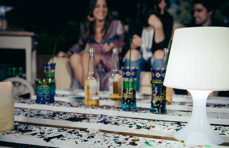 White lamp over pallets table with confetti in outdoors party