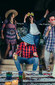Happy friends dancing and having fun with costumes in party