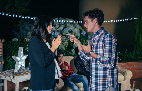 Couple arguing having a quarrel in night party