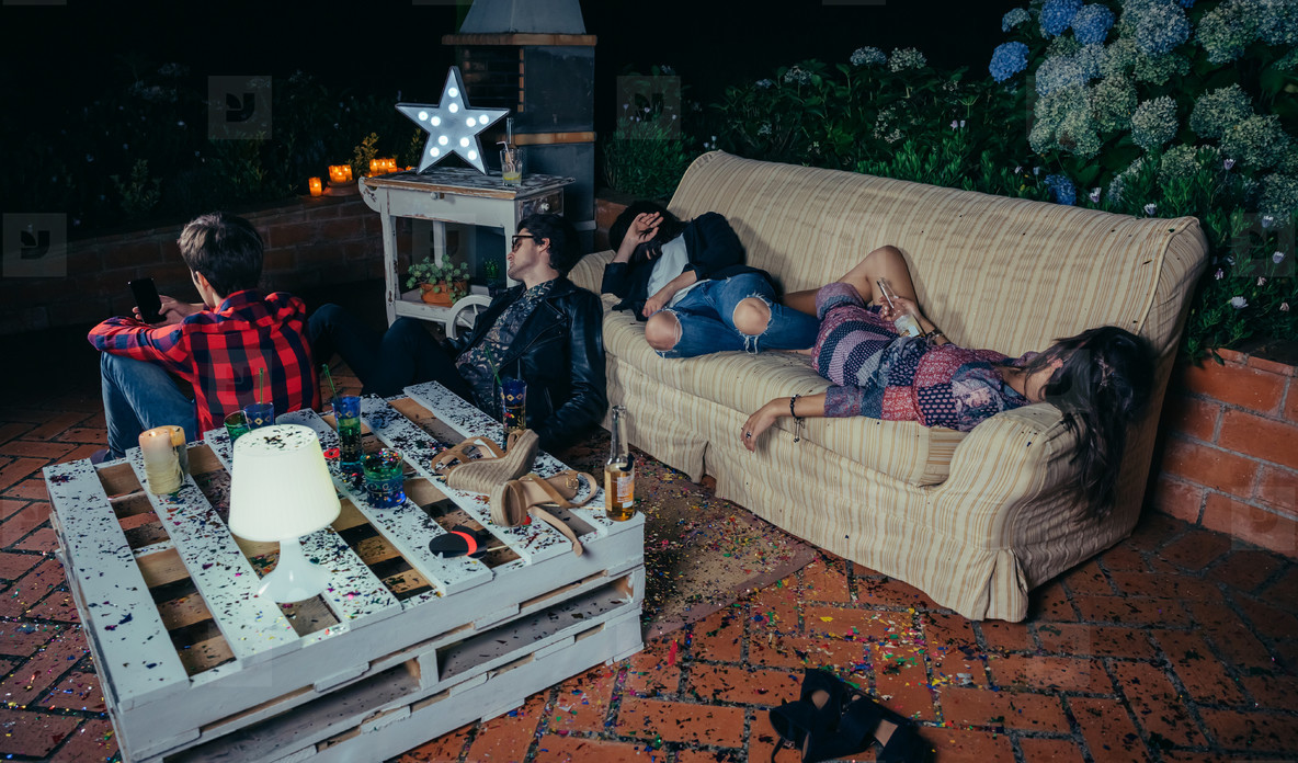 Young drunk friends sleeping in a sofa after party