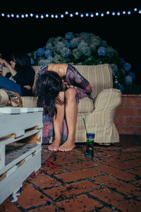Young drunk woman sitting in the sofa on a party