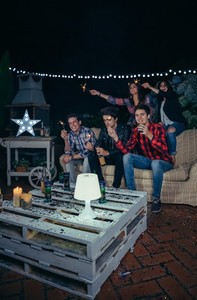 Happy friends holding sparklers in a night party