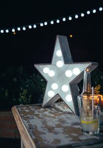 White star lamp with light bulbs over table
