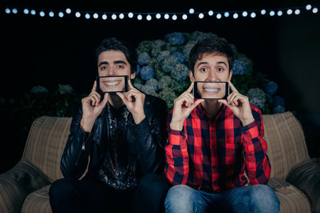 Funny young men holding smartphones showing female mouths smiling