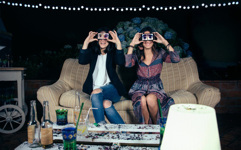 Funny young women holding smartphones showing male eyes