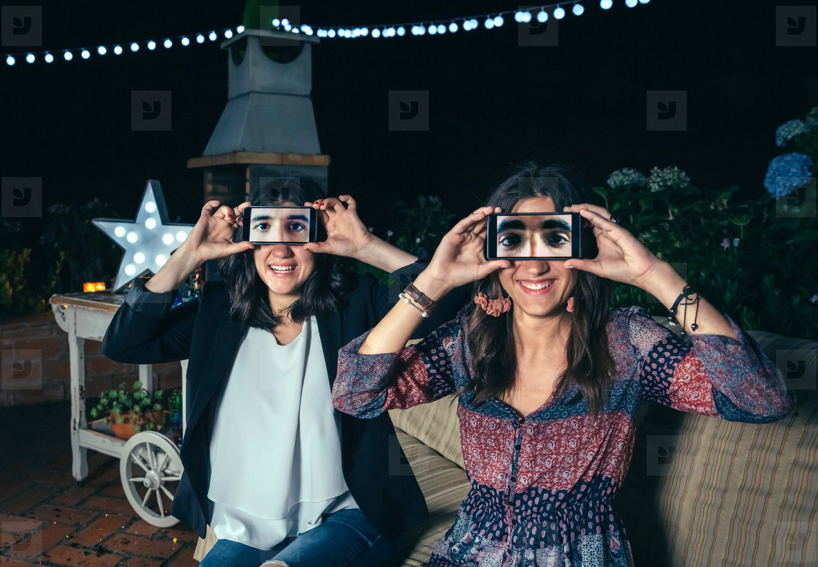 Funny women holding smartphones showing male eyes