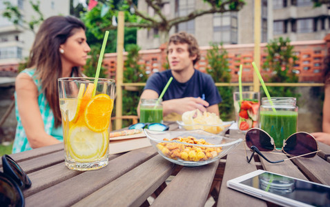 Infused fruit water cocktails and people talking in background