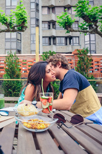Young man whispering to woman sitting outdoors