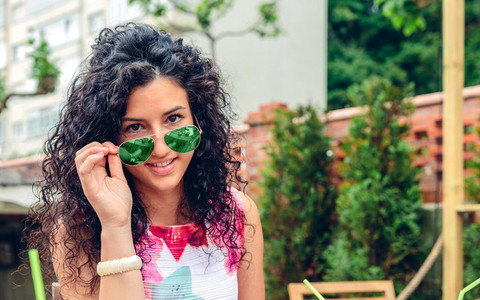 Smiling young woman looking at camera over sunglasses