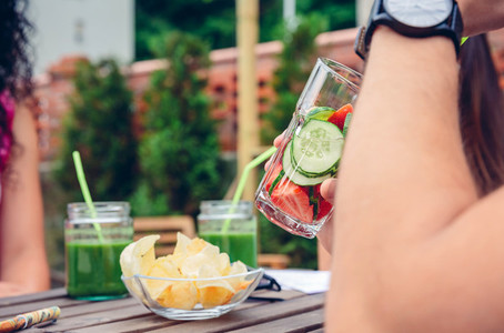 Man drinking infused fruit water cocktails outdoors