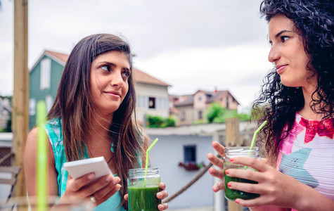 Two women looking at each other and holding green smoothies