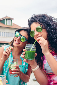Two women with sunglasses drinking organic beverages outdoors