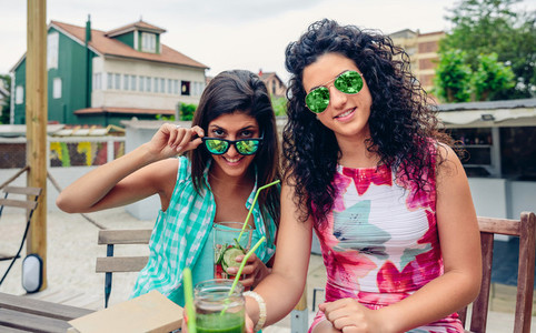 Two women with sunglasses and beverages looking at camera