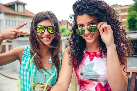 Two women with sunglasses and smoothies looking at camera
