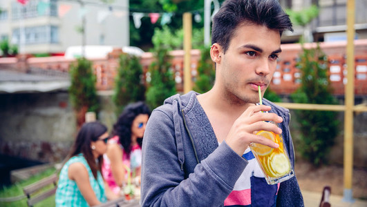 Young man drinking infused water cocktail outdoors