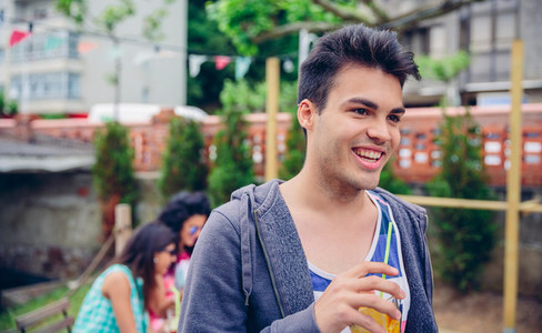 Young man holding glass of infused water cocktail outdoors