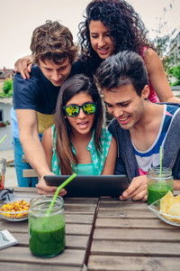 Young happy people looking tablet over table