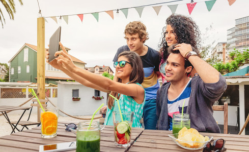 Group of young people taking a selfie with tablet