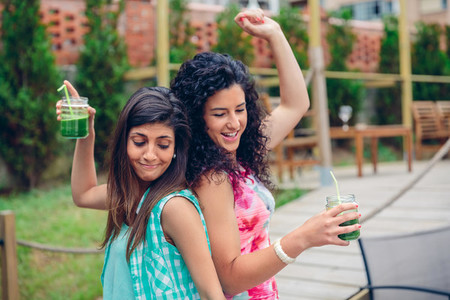 Young women couple with healthy drinks dancing outdoors