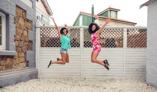 Happy women jumping in front of garden fence
