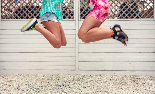 Unrecognizable women jumping over garden fence background