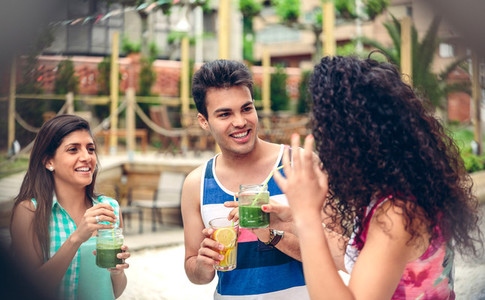 Young people laughing and drinking in summer party
