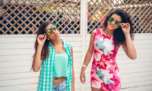 Women with sunglasses looking at camera over garden fence