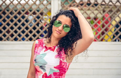 Woman with sunglasses looking at camera over garden fence