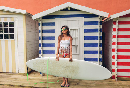 Young surfer woman with top and bikini holding surfboard