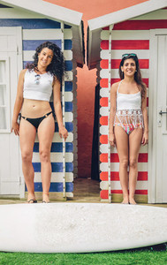 Young surfer women couple with bikini and surfboard