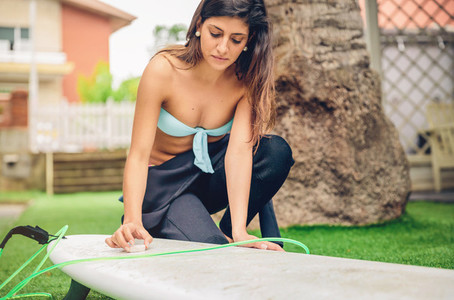 Surfer woman with bikini and wetsuit waxing surfboard