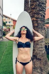 Brunette surfer woman in bikini standing with surfboard