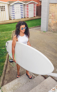 Brunette surfer woman with top holding surfboard