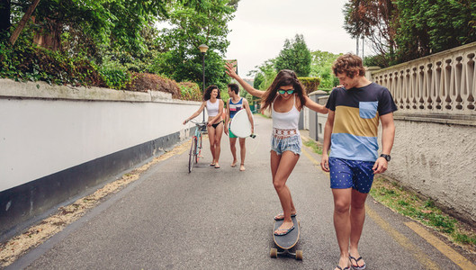 Happy young woman riding on skate with her friends