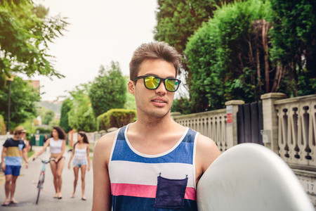 Close up of young man with sunglasses holding surfboard