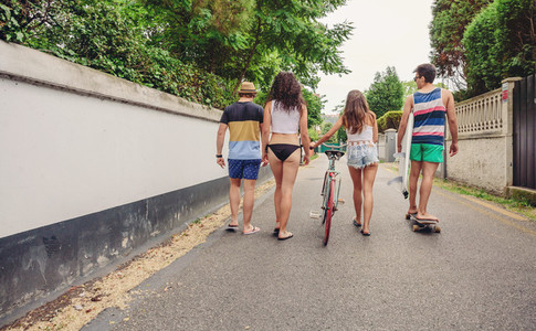 Back view of young people walking along road