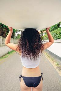 Brunette girl holding surfboard over head on street