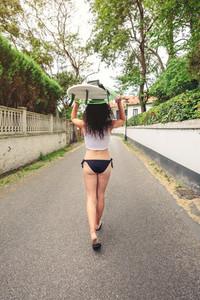 Brunette girl holding surfboard over head and walking