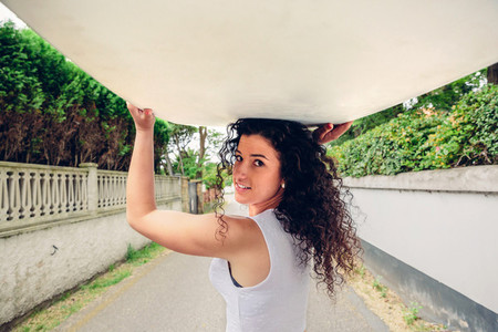 Smiling brunette girl holding surfboard over her head