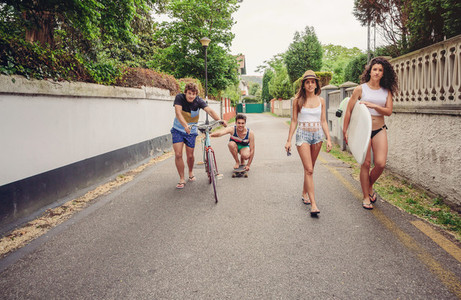 Happy young people having fun with skateboard and bicycle