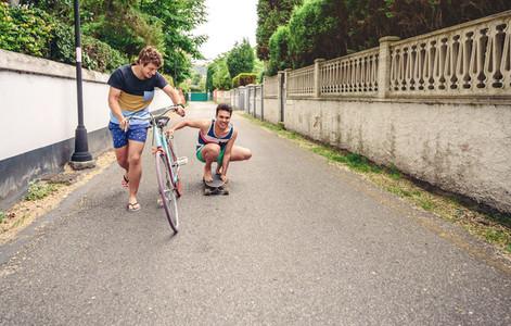 Two men having fun riding bike and skateboard