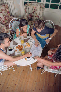 Group of young friends looking maps and enjoying breakfast