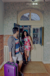 Young couple with suitcases arriving to a hostel