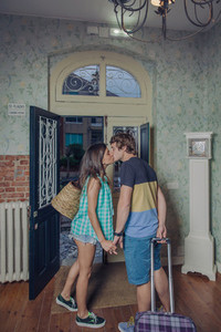 Couple in love with suitcases kissing at hostel entrance