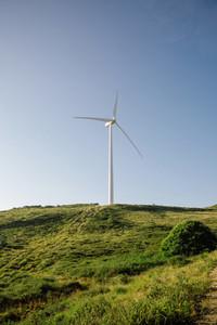 Wind turbine generating electricity over blue sky background