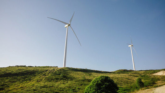Wind turbines generating electricity over blue sky background